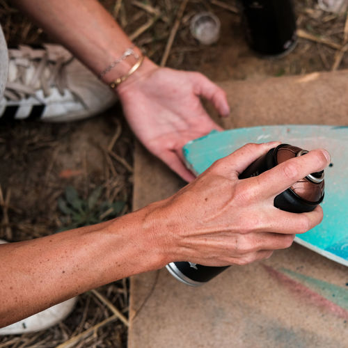Cropped Hand Of Woman Using Spray Paint