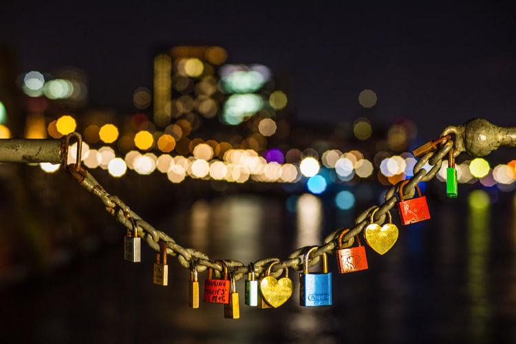 Close-Up Of Colorful Padlocks Hanging At Night