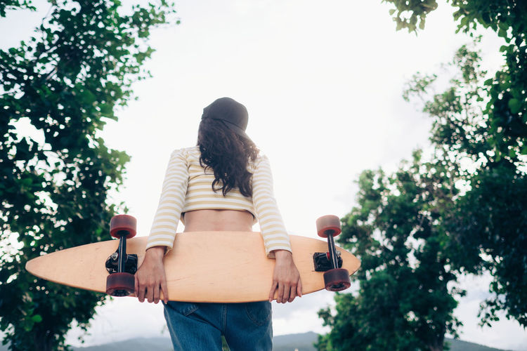 Rear view of woman holding skateboard while standing against trees