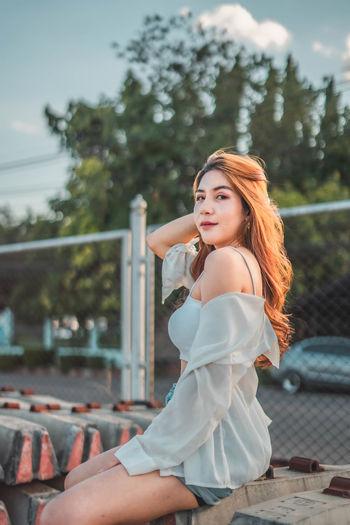 Beautiful young woman sitting outdoors
