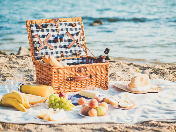Closeup of picnic basket with drinks, wine, fruits on sand beach near sea Basket Beach Cheese Container Day Food Food And Drink Freshness Fruit Healthy Eating Land Nature No People Outdoors Picnic Picnic Blanket Sea Still Life Table Water Wellbeing