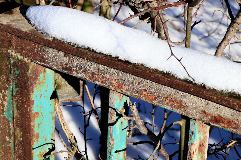 Low angle view of snow on rusty metal during winter