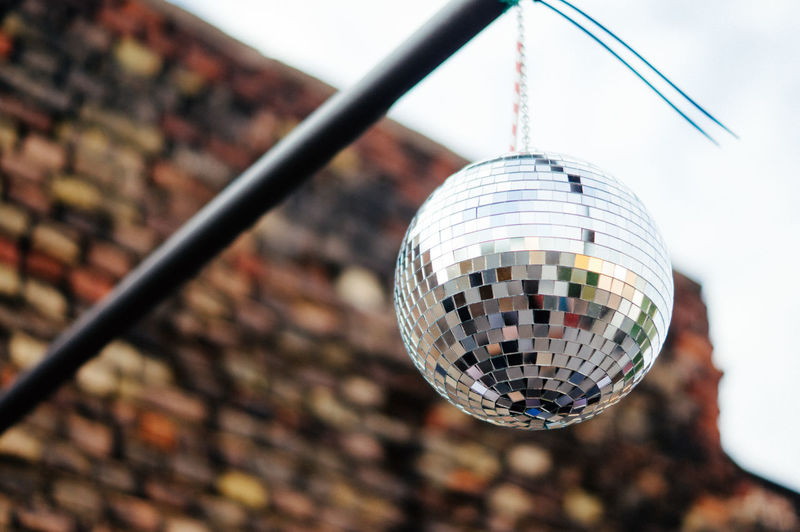 Low angle view of disco ball hanging outdoors