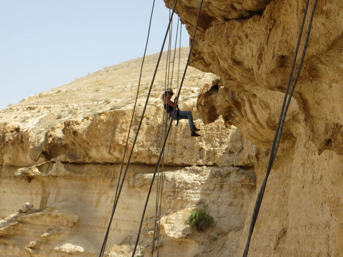 Woman climbing rock against clear sky