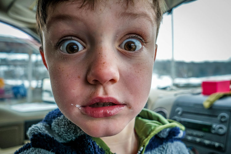 Close-up portrait of shocked boy in car