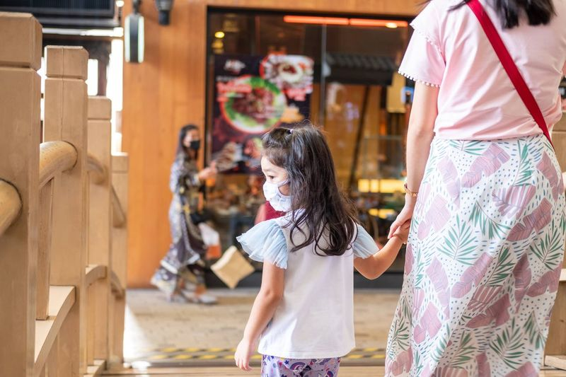 Rear view of daughter wearing mask walking with mother