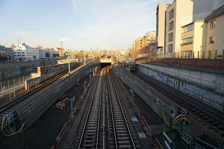 High angle view of subway tracks amidst buildings in city while sunset