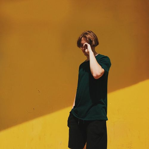 Man looking away against yellow wall