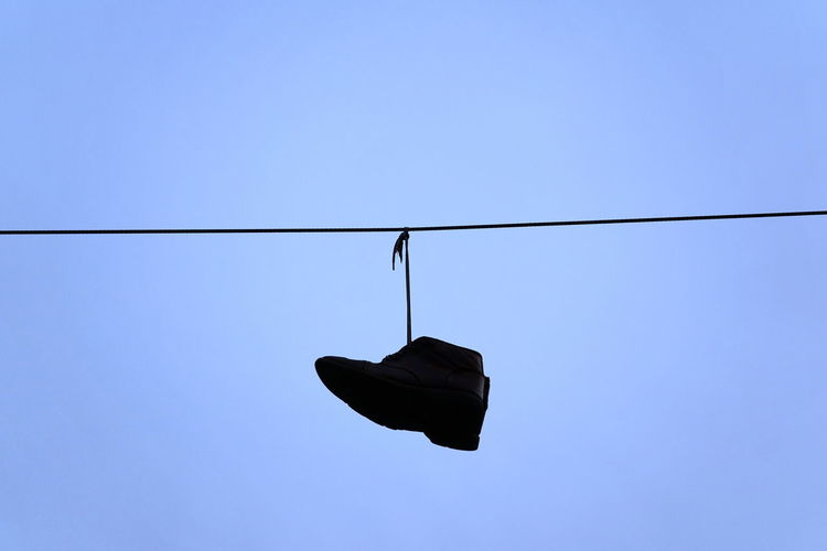 Low angle view of shoes against clear blue sky
