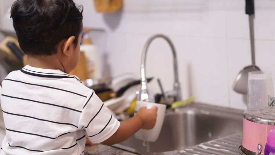 Rear view of boy with faucet in water at home