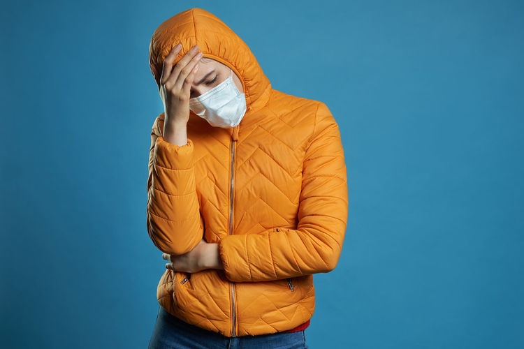 Woman standing against blue background