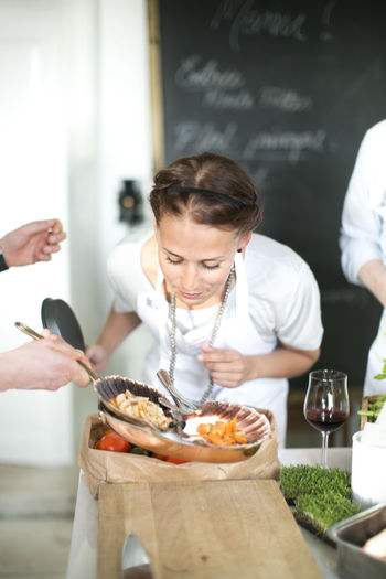 Woman holding food on table in restaurant