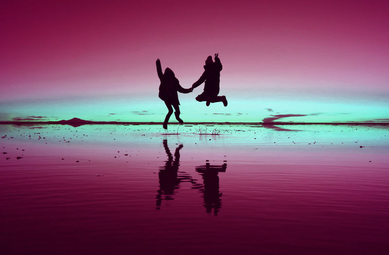 Pop art styled silhouette of happy couple jumping on the mirror effect of uyuni salt flats, bolivia
