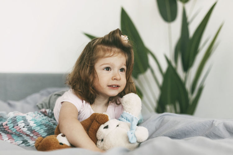 Portrait of a charming little girl lying on a bed with her teddy bear