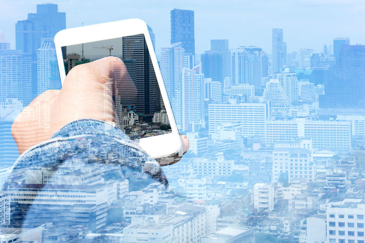 Digital composite image of hands holding smart phone against cityscape