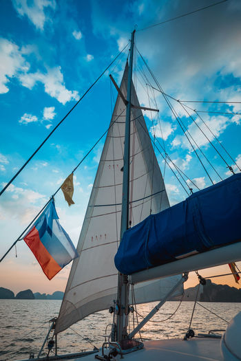 Cloud - Sky Sky Sailboat Nature Transportation Mode Of Transportation Water Day Nautical Vessel Blue Mast Flag Sea Pole Rope Low Angle View Outdoors Patriotism Environment Wind