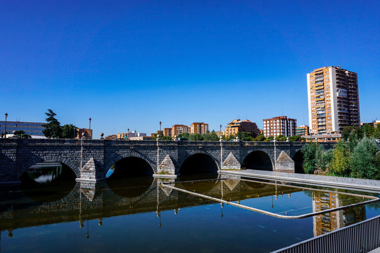 Bridge over river in city against clear blue sky