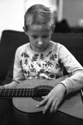 """""""My beautiful son playing guitar"""" Film Photography Filmisnotdead 35mm Film 35mmfilmphotography Analog Analogue Photography Olympus Trip 35 Olympus Blackandwhite Blackandwhite Photography Blackandwhitephotography Black And White Black And White Photography EyeEm Best Shots - Black + White Guitar Portrait Childhood Playing Music Child Sitting Arts Culture And Entertainment Musical Instrument Classical Guitar Acoustic Guitar Musical Instrument String The Portraitist - 2018 EyeEm Awards"""