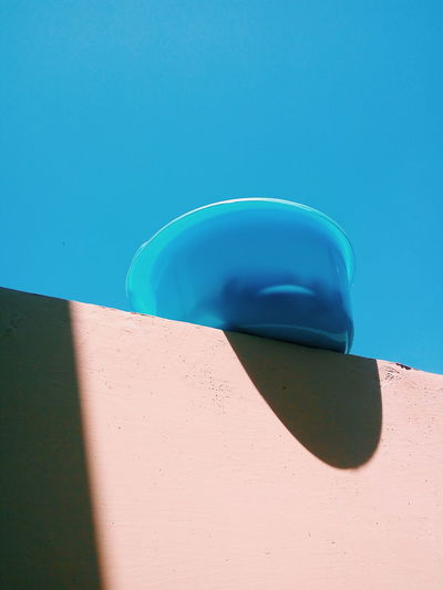 Low angle view of bowl on retaining wall against clear sky