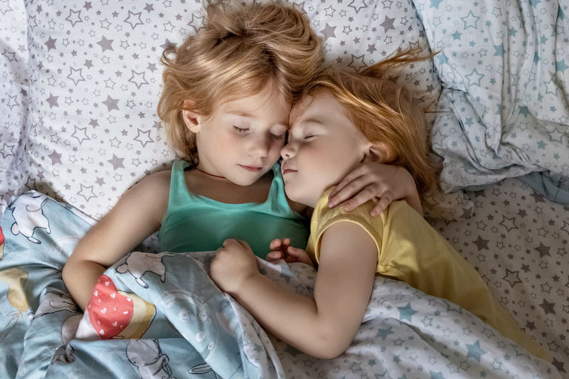 High angle view of sisters sleeping on bed at home