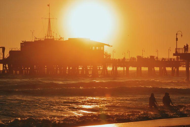 People Enjoying At Sea Against Santa Monica Pier During Sunset
