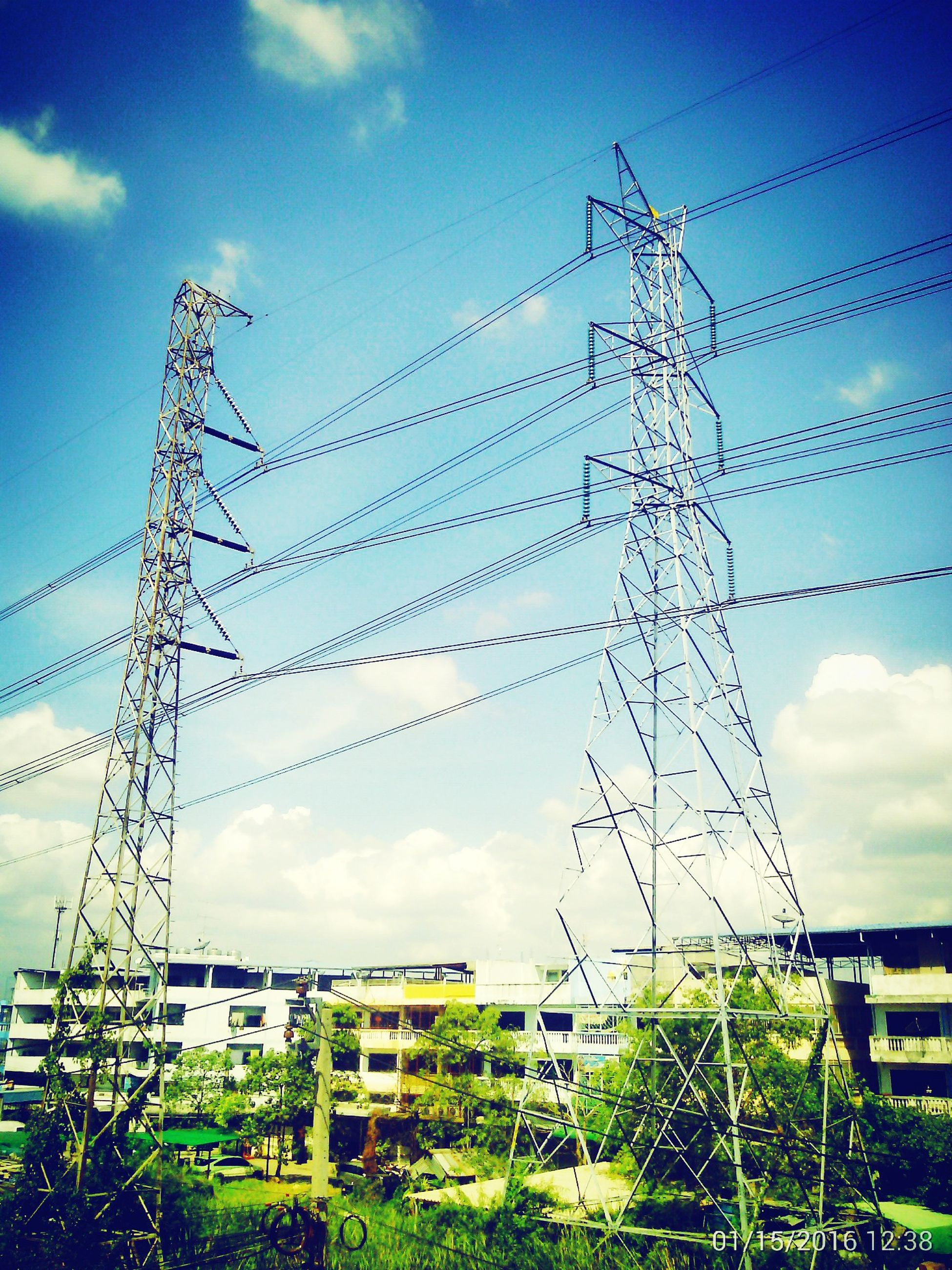 electricity pylon, power line, power supply, electricity, sky, fuel and power generation, building exterior, cable, low angle view, built structure, connection, technology, architecture, cloud - sky, cloud, field, day, no people, outdoors, growth