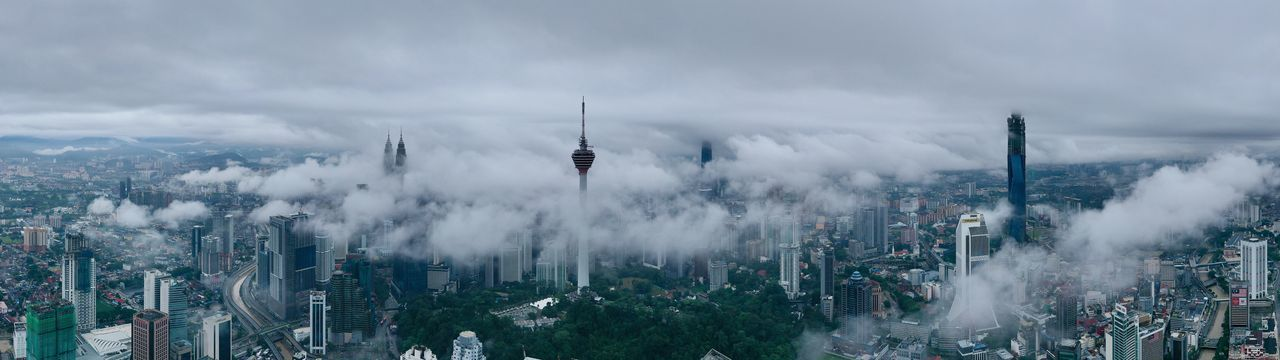 Panoramic view of cityscape against cloudy sky