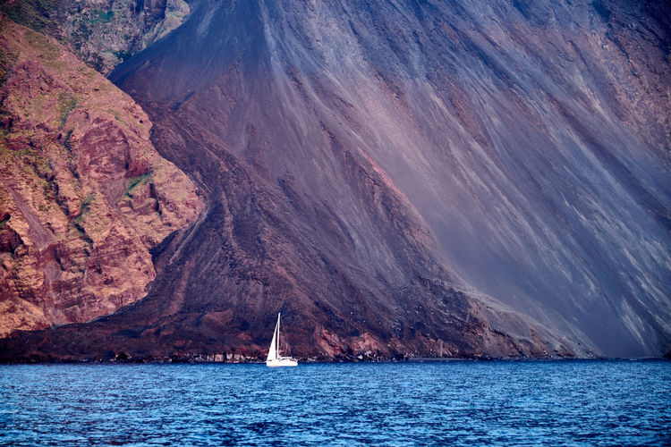 The sea and the telluric rock in Aeolian Islands - Vesuvius - Aeolian Islands Beauty In Nature Blue Boat Exploring Mountain Mountain Range Nature Nautical Vessel Rock Formation Sailboat Sailing Scenics Sea Sicily Vesuvio Water Waterfront The Great Outdoors With Adobe