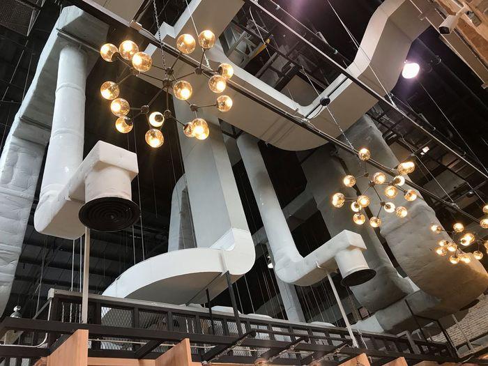 Low angle view of illuminated lighting equipment at restaurant