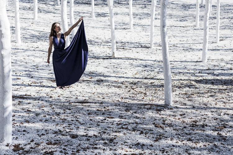 Woman in dress walking amidst trees