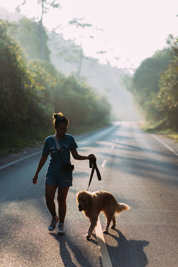 Woman walking with dog on road during morning