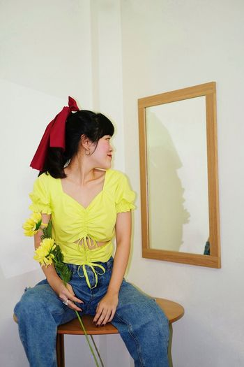 Midsection of woman holding while sitting against wall at home