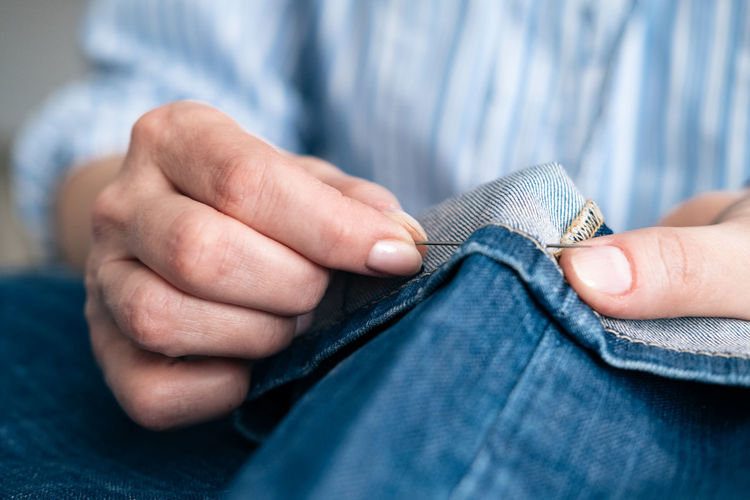 Human Hand Jeans Midsection Hand Indoors  Close-up Finger Needle Sewing Seamstress Jeans Denim Hem Adult Art And Craft Menswear Holding Blue Wool Selective Focus Human Body Part Textile