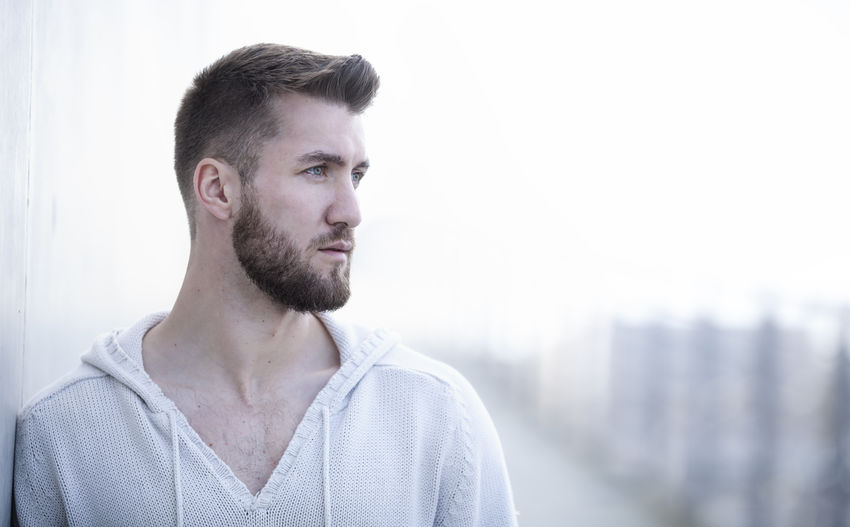 Portrait of an attractive man with a white pullover Adult Beard Bearded Casual Clothing City Close-up Day Fashion Handsome Headshot Human Isolated Lifestyles Looking Model One Person Outdoors People Portrait Profile T-shirt Thinking Urban White Background Young Adult