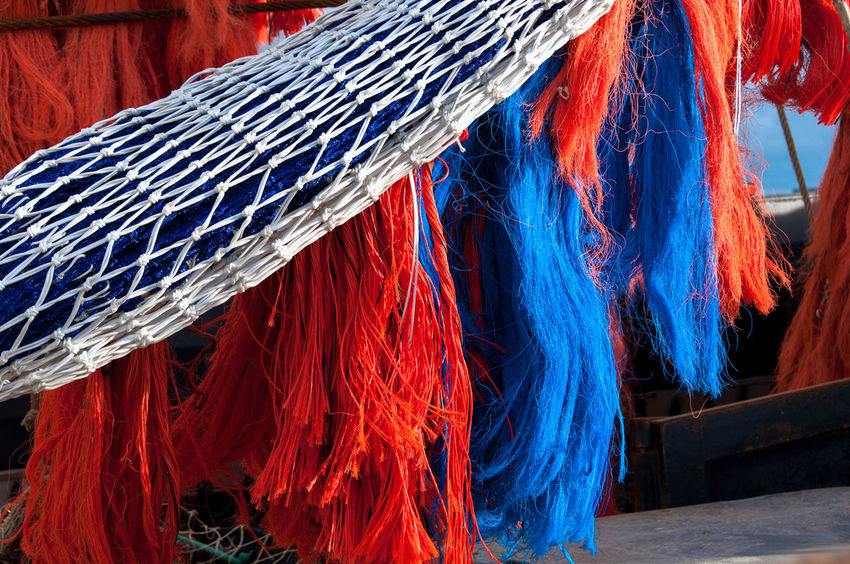 Textile Close-up Multi Colored No People Red Day Equipment Cleaning Wool Fishing Net Thread Rope Housework Material Hanging Outdoors Blue Focus On Foreground Chores Industry Fishing Industry Tangled