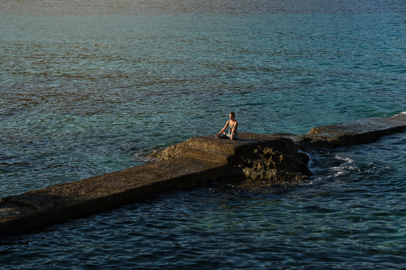 Man standing on rock by sea