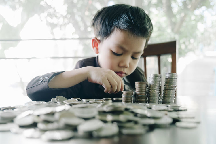 Cute Boy Stacking Coins On Table