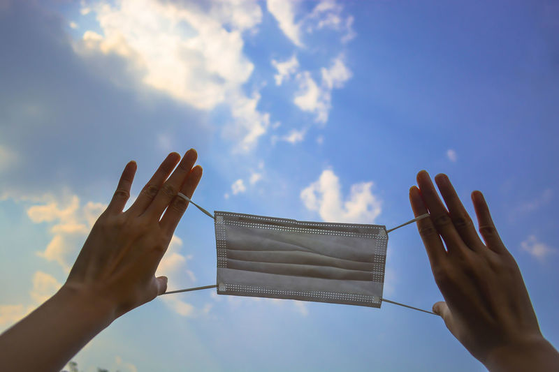 Low angle view of hand holding umbrella against sky