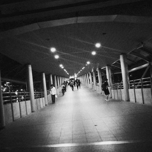 Chong Nonsi Skywalk at Bangkok, after work in the night period. darkness and light HUAWEI Photo Award: After Dark Dark Monotone Monochrome Citylife Nightlife Blackandwhite Night Afterwork Pathway Walkway People Walk Illuminated In A Row Lighting Equipment Ceiling Architecture Underpass Tiled Wall Hand Rail Pillar Column Ceiling Light  Transportation Building - Type Of Building
