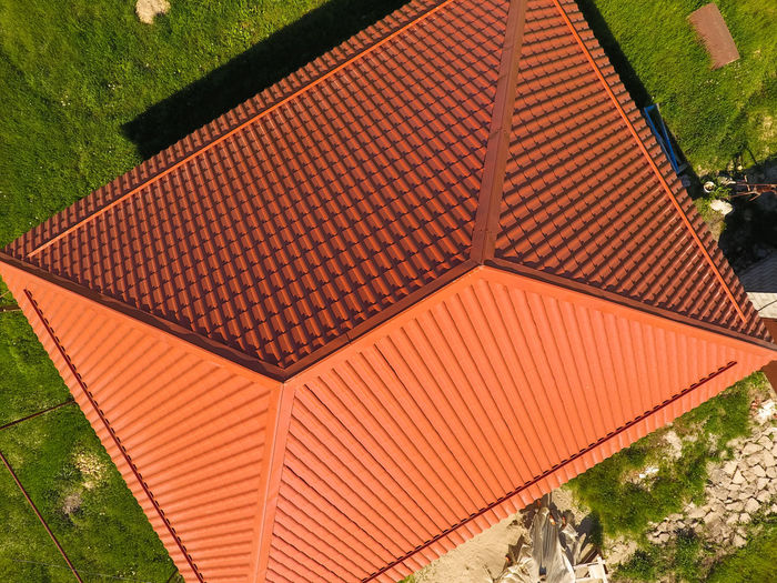 red, orange roof corrugated sheets Architecture Building Building Exterior Built Structure Day Design High Angle View House Nature No People Orange Color Outdoors Pattern Plant Roof Roof Tile Shape Sunlight Tree