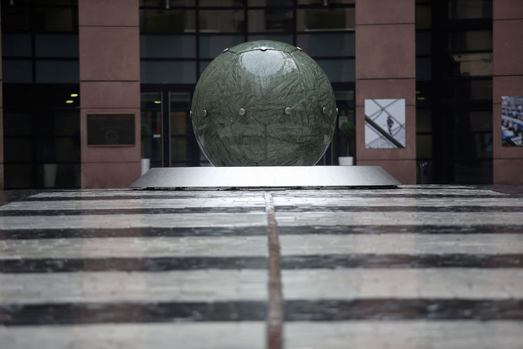 Close-up of glass ball on table against building in city
