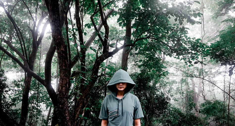 Man with hooded shirt standing against trees in forest