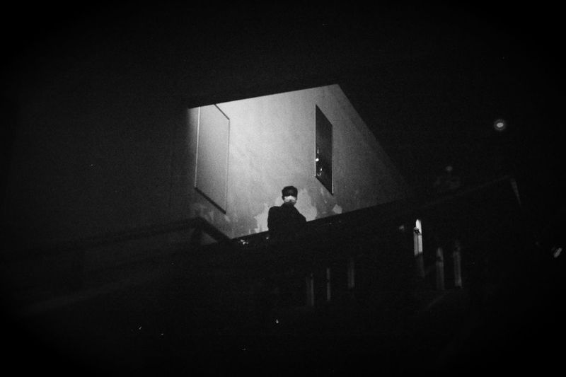 Low angle view of silhouette man standing against building