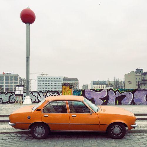 Vintage car on city street against sky