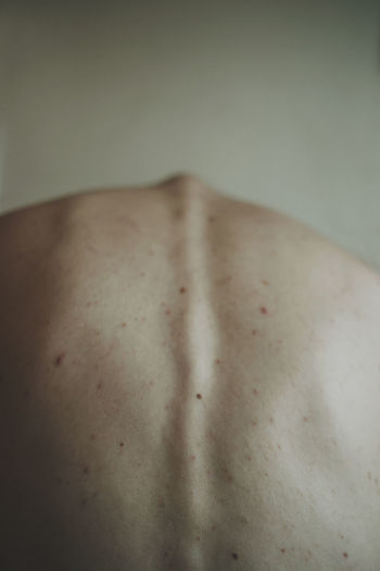 Close-up of midsection of shirtless man back at home