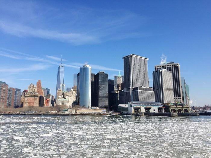 Urban skyline by frozen east river against sky