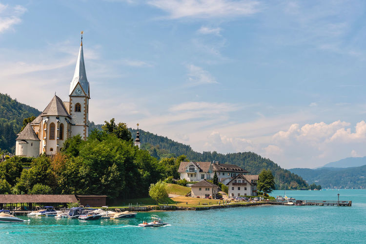 WORTHERSEE, AUSTRIA - AUGUST 08, 2018: View of the Worthersee lake with Maria Worth church, Carinthia, Austria Nature Day Outdoors Austria Carinthia Carinthian Lakes Tourist Tourists Lake Wörthersee Recreation  Leisure Landscape Water Sea Boats Motorboat Speedboats Summer People Holidays Fun Travel Beach Resort Lifestyle Sunny Rest Joy Waves Europe Alps Alpine Alpine Lake Built Structure Architecture Building Exterior Religion Place Of Worship Spirituality Building Sky Belief Tree Nautical Vessel Cloud - Sky Transportation Spire  Sailboat Church