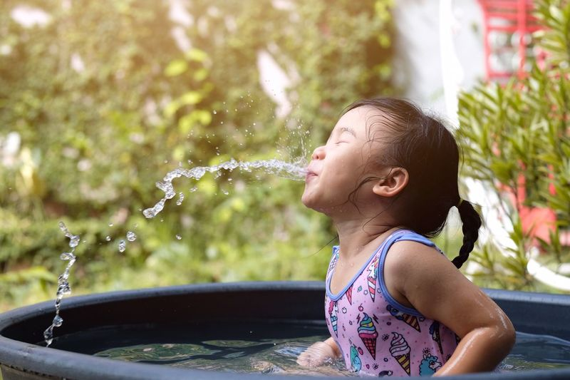 Close-up of girl spraying water with mouth while sitting in wading pool