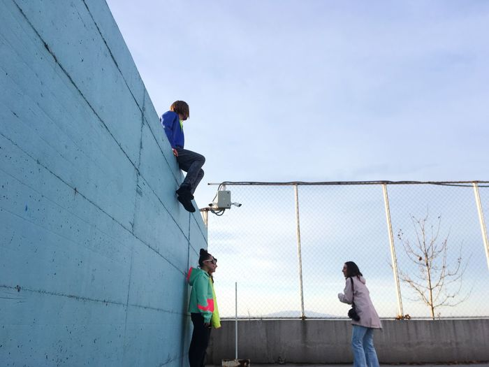 Friends On Building Terrace Against Clear Sky