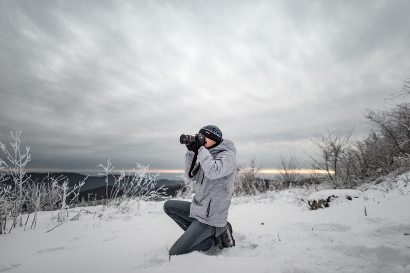 Cloudy Beauty In Nature Camera - Photographic Equipment Cloud - Sky Clouds And Sky Cold Temperature Day Field Full Length Men Nature Outdoors Photographing Photography Themes Portrait Real People Sky Snow Technology Togetherness Two People Warm Clothing Weather Winter Young Adult